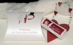 Liebevoll gestaltete Hochzeitseinladung mit den Initialen des Brautpaares sowie einem Schleier und Hut in tollem rot