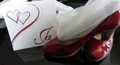 Stilvolle Hochzeitseinladung mit bezaubernden Herzen in traumhaften rot