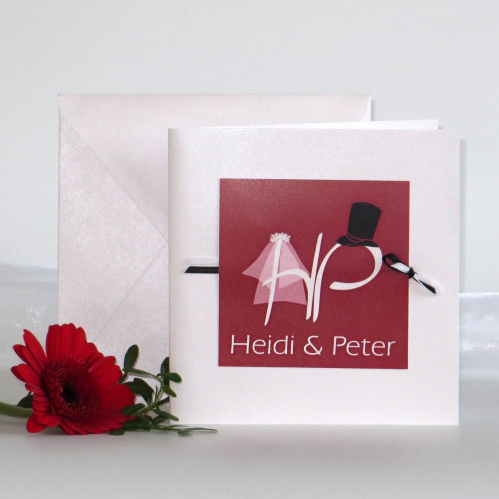 Moderne Hochzeitseinladung mit den Initialen des Brautpaares in rot.