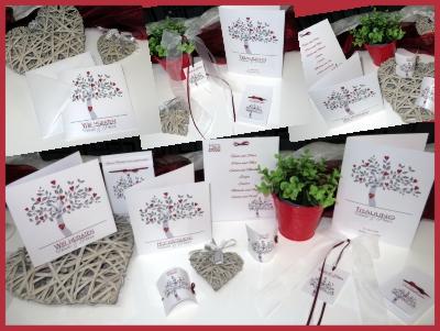 Hochzeitskarten mit einem silbernen Baum als Mittelpunkt, mit roten Herzen und den Initialen des Brautpaares