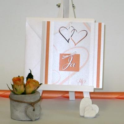 Hochzeitseinladung mit Initialen und einer kleinen Schleife.
