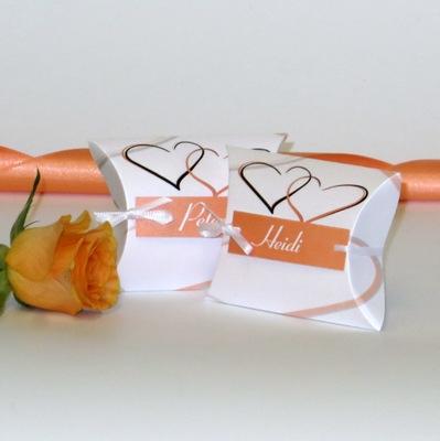 Kartonagen für Gastgeschenke mit orangen Herzen.