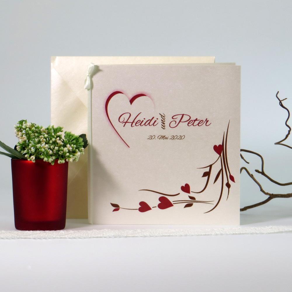 Edle Hochzeitseinladung mit einem Motiv aus Ranken und Herzen in rot und braun.