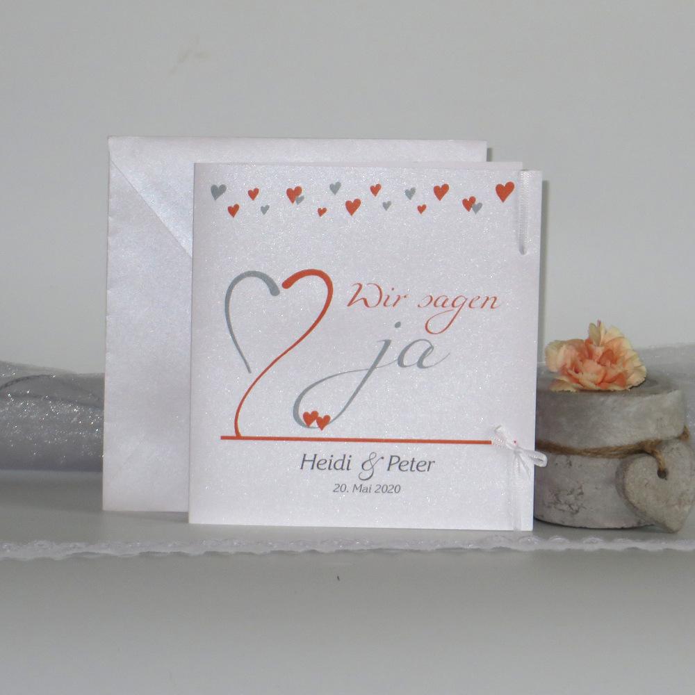 Hochzeitseinladung mit einer Herzblume in orange und grau