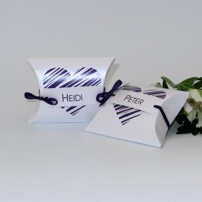 Süße Kisschenschachteln mit einem Aufdruck in lila als Tischkarte bei der Hochzeit