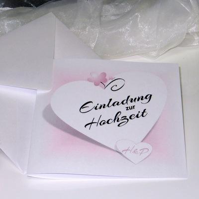 Romantische rosa Hochzeitseinladung mit Herzen, einer Blume und einem Schmetterling.