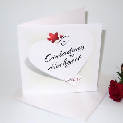 Hochzeitseinladung mit einem weißen Herz und roten Details wie einer Blume und einem Schmetterling.