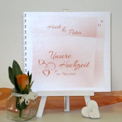 Mit einem Farbverlauf in orange gestaltetes Hochzeitsgästebuch.