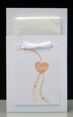 """Freudentränen mit einer hübschen Schleife und dem Aufdruck """"Love"""" in einem Herz in apricot."""