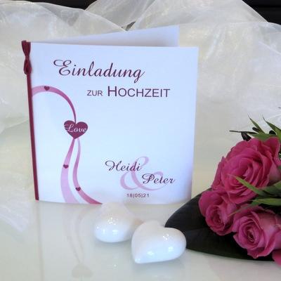Hochzeitseinladung in pink und weiß mit Herzen und weiteren besonderen Details.