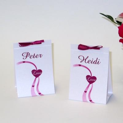 Tischkarten in pink und weiß mit einer pinken Schleife.