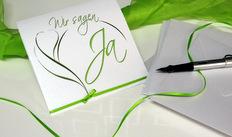 Moderne Hochzeitseinladung mit einem Design in grün und weiß.