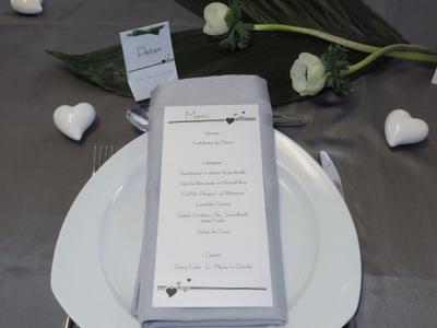Hochzeitsmenükarte in grau und weiß mit kleinen grünen Herzen.