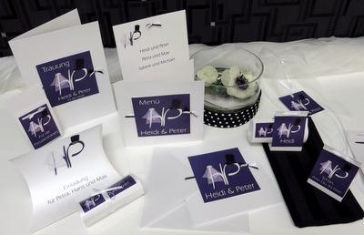 Extravagante Hochzeitspapeterie mit den Initialen des Brautpaares in lila.