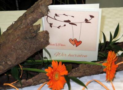 Extravagante Einladungskarte zur Hochzeit mit einem Design in orange und braun.