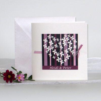 In ausgefallener Farbe aubergine präsentiert sich diese Hochzeitskollektion mit Blumen, die ein Herz bilden.
