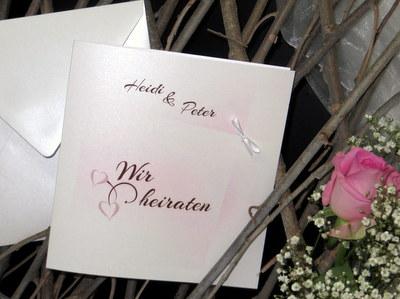 Außergewöhnliche Einladungskarte zur Hochzeit mit passender Deko in rose und braun.